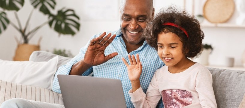 grandpa and granddaughter video call on laptop