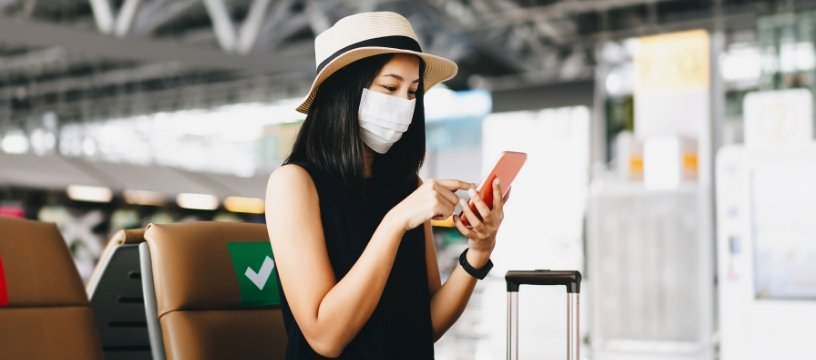 asian woman at airport with covid mask