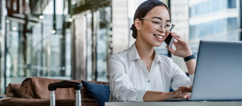 asian woman on phone working on laptop