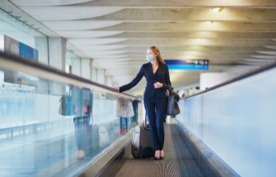 Female business traveller with COVID mask at airport