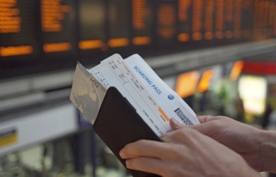 Male travellers checking boarding pass at airport