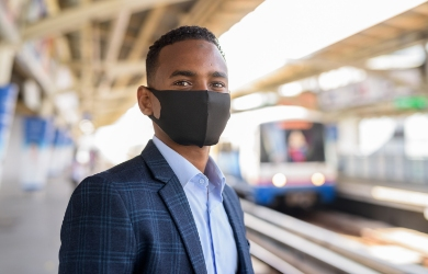 Male business traveller with mask catching train