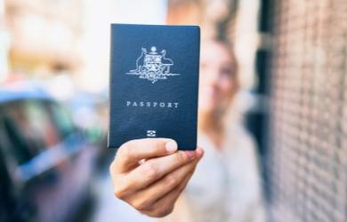 Female holding up Australian passport