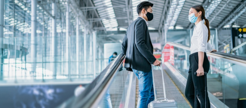 Asian travellers at airport with COVID masks
