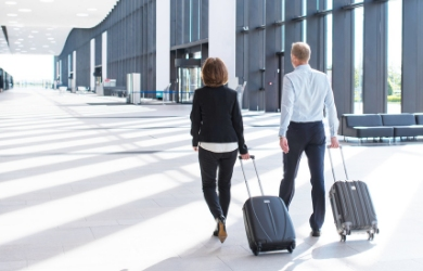 Business travellers at airport with suitcases