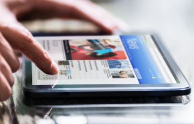 Male reading news on tablet