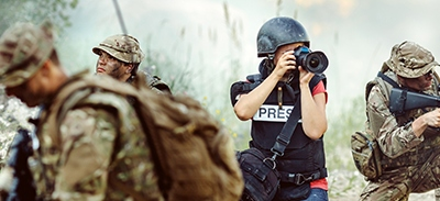 Journalist in war zone avoiding risk